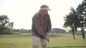Golfeur mûr réussi de portrait balançant et frappant la boule de golf sur le beau cours Homme sûr jouant au golf dans beau clips vidéos