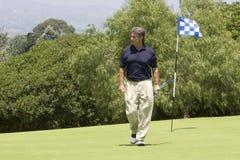 Golfeur marchant outre du vert Images libres de droits