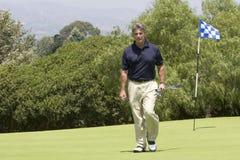Golfeur marchant outre du vert   Image libre de droits