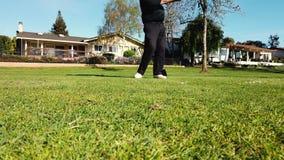 Golfeur mettant la boule de golf pour trouer sur le terrain de golf vert sur des collines en concours général de tournoi Joueur t banque de vidéos
