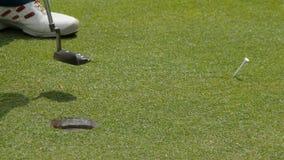 Golfeur professionnel mettant la boule dans le trou Boule de golf par le bord du trou avec le joueur à l'arrière-plan un jour ens clips vidéos