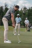 Golfeur visant à frapper une boule avec le club pendant le jeu avec ses amis Photos stock