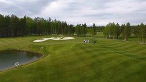 Golfeurs frappant le tir de golf avec le club sur le cours tandis que des vacances d'été, aériennes Photos stock