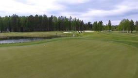 Golfeurs frappant le tir de golf avec le club sur le cours tandis que des vacances d'été, aériennes Photo stock