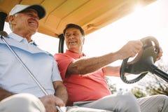 Golfeurs supérieurs dans un chariot après parcours de golf le jour ensoleillé photographie stock