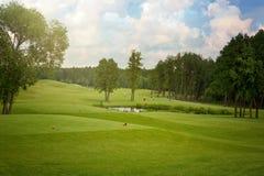 Golffält med träd över molnig himmel Royaltyfri Fotografi