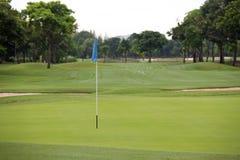 Golffeld mit Lochflagge Stockfotos