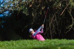 Golfflickan stryker följer igenom Arkivfoto