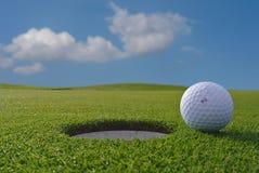 Golfgat en bal Stock Foto's