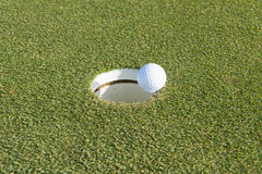Golfgat op een gebied en een golfbal Royalty-vrije Stock Afbeeldingen