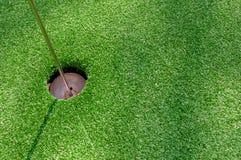 Golfgat op groen met kunstmatig gras Stock Afbeelding