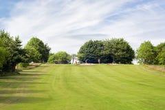 Golfgebied en drie unrecognisable golfspelers bij een afstand royalty-vrije stock foto's
