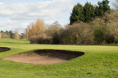 Golfgräsplan och en sandbunker på en Sunny Day Arkivfoton