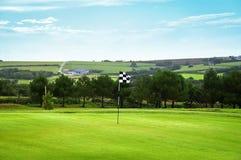 Golfgrün mit einer checkered Markierungsfahne Stockfoto