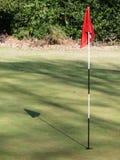 Golfgrün mit werfendem Schatten der roten Fahne stockfotos