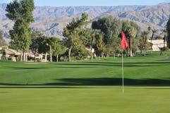 Golfgrün mit einer roten Fahne und einer Fahrrinne Stockbild