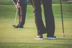 Golfgrün sceen - den Golfspieler, der nahe dem Loch, kurzen Schlag sich setzt Lizenzfreies Stockfoto