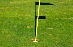 Golfhål på en gräsplan med hålmaterielet och skugga av flaggan Arkivbild