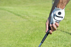 Golfhandske och pinne Arkivbild