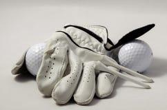 Golfhandske, utslagsplatser och en golfboll Royaltyfri Fotografi