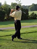 Golfing. Man on golf course - swing complete - rear view stock photo