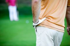 Golfing. Golfer waiting for his turn, focus on hand Royalty Free Stock Images