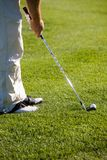 Golfing. Golfer getting ready to hit the ball Royalty Free Stock Images