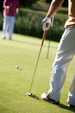 Golfing. Golfers playing golf on beautiful sunny day Stock Image