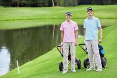 Golfing. Two men on golf course Royalty Free Stock Photo