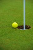 Golfing. Ball rests at rim of cup. So close Royalty Free Stock Photography