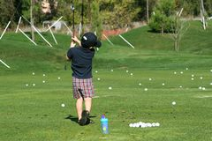 Golfing. Boy at the driving range Stock Photo