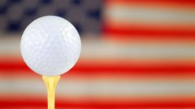 Golfing In america. Golf Ball on Gold Tee with Flag in Distance Royalty Free Stock Images