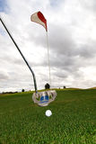 Golfing in bad weather. A golfer putting in stormy weather stock photography