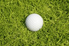 Golfing. A ball on the green grass background Stock Photos