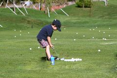 Golfing Boy. Hitting balls at the driving range Royalty Free Stock Image