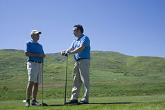 Golfing Buddies. Two men talk together while waiting on the tee box at the golf course. It looks like they are talking business Royalty Free Stock Images