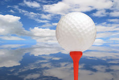 Golfing challenge. Golf ball on red tee with sky reflected on ground Royalty Free Stock Image