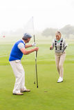 Golfing couple cheering on the putting green Stock Photography