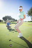 Golfing couple cheering on the putting green Royalty Free Stock Photos