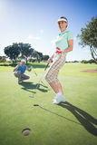 Golfing couple cheering on the putting green Royalty Free Stock Photo