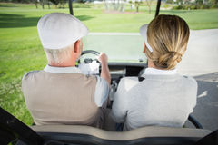 Golfing couple driving in their golf buggy Royalty Free Stock Photo