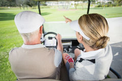 Golfing couple driving in their golf buggy with woman pointing Royalty Free Stock Images