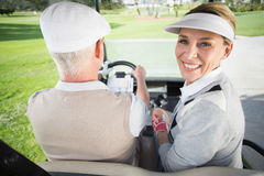 Golfing couple driving in their golf buggy with woman smiling at camera. Golfing couple driving in their golf buggy with women smiling at camera on a sunny day royalty free stock photos