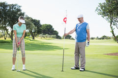 Golfing couple at the eighteenth hole on the golf course Stock Photography