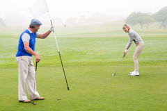 Golfing couple on the golf course Royalty Free Stock Images