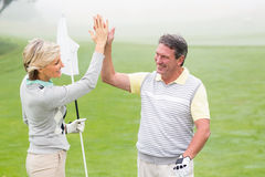 Golfing couple high fiving. On a foggy day at the golf course Stock Image