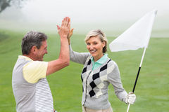 Golfing couple high fiving Stock Image