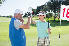 Golfing couple high fiving on the golf course at eighteenth hole Royalty Free Stock Photos