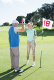 Golfing couple high fiving on the golf course at eighteenth hole Stock Image