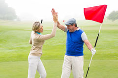 Golfing couple high fiving on the golf course. On a foggy day at the golf course Stock Photography